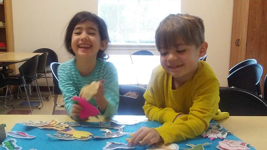 Two students smile and use teamwork on a dinosaur project.